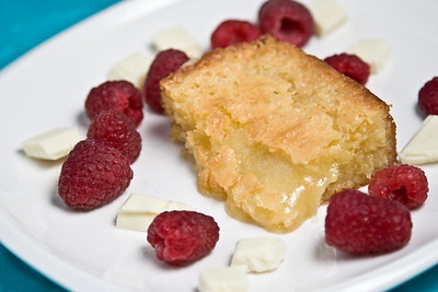 white chocolate brownie on plate with raspberries